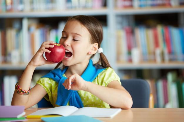 Menina comendo maçã no lanche para escola